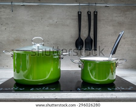 Two green enamel stewpots on black induction cooker - stock photo