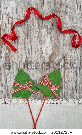 Two green fir tree with ribbon on old wood background