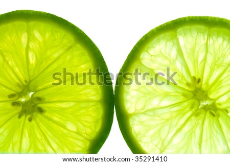 Two green lime slices, back lit and isolated on white background.