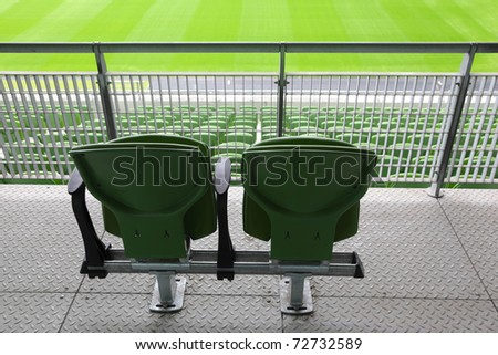 Two green plastic seats on tribune of large stadium, behind - stock photo