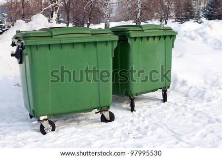Two green recycling containers in winter park - stock photo