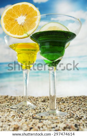 two green yellow fruity cocktails with lime slice on the sand with the sea beach ocean in the background  - stock photo