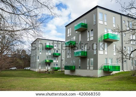 Two grey apartment houses with a green garden. Modern houses with glass bright green balconies. Row of buildings in urban style. Stockholm, Sweden. Big grass lawn in  foreground. Place for your text.  - stock photo