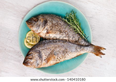 Two grilled barbeque sea bream on plate with fresh rosemary herbs and lemon on white wooden background. Culinary mediterranean seafood eating. - stock photo