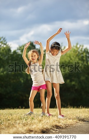 Two grils dancing in summer at the park