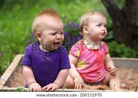 two grubby kids playing in the sandbox - stock photo