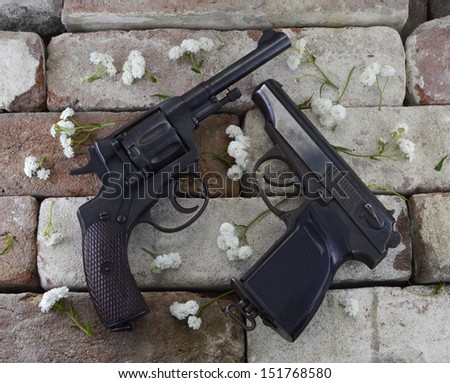 Two guns with flower petals on stone background - stock photo
