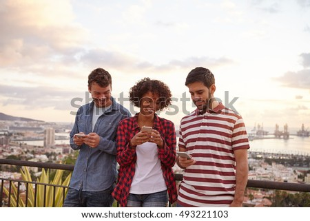 Two guys and a girl looking at their cellphones while standing on a bridge overlooking a city wearing casual clothing
