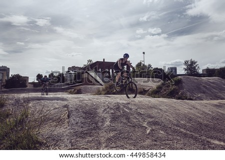 Two guys are riding a bicycles on sand tracks in the summer