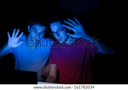 Two guys greeting someone through a video chat - stock photo