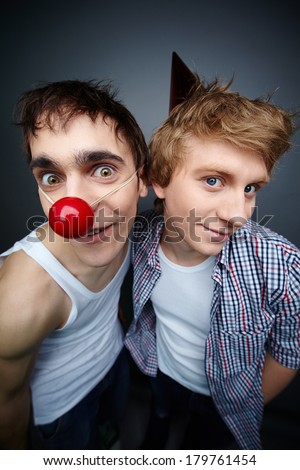 Two guys having fun making faces at camera on fools day - stock photo