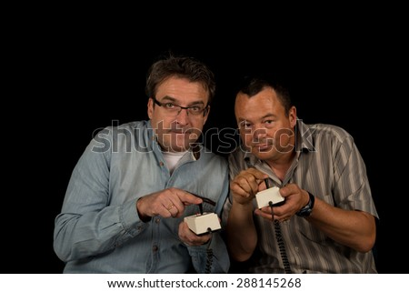 Two guys holding some retro video game controls - stock photo