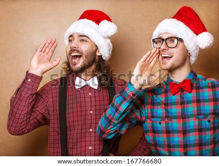 two guys in hipster clothes of Santa Claus in a Christmas shout