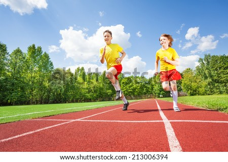Two guys running together in competition - stock photo