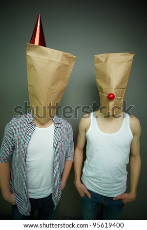 Two guys standing in front of camera in paper bags celebrating fool�s day - stock photo