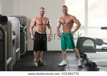 Two Guys Standing Strong In The Gym And Flexing Muscles - Muscular Athletic Bodybuilder Fitness Model Posing After Exercises - stock photo