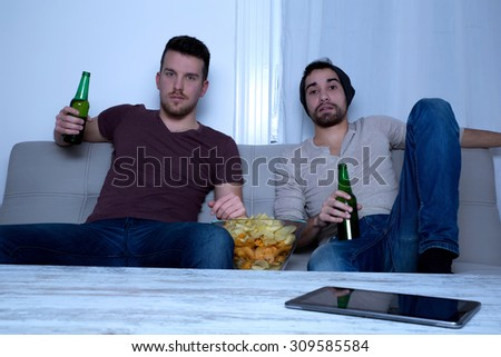 Two guys watching tv, drinking beer, eating crisps at home - stock photo