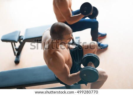 Two guys working out in gym
