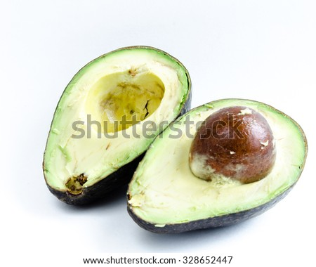 Two half cuts/slices with seed of organic fresh ripe avocado isolated on white background