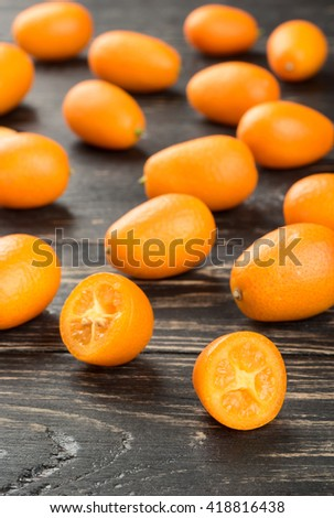 Two half kumquat with scattered fruit on the table