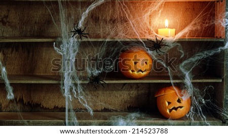 Two Halloween Jack o Lanterns Carved from Oranges and Spiderwebs with Spiders and Lit Candle on Shelves - stock photo