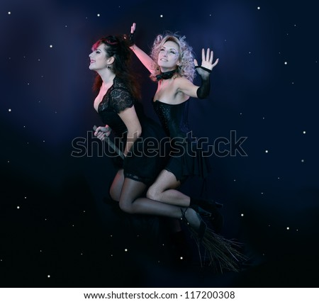 two halloween witches flying on broom on a dark sky with stars - stock photo