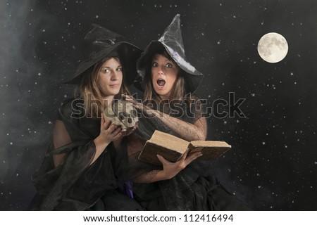 two halloween witches on dark smoke background - stock photo
