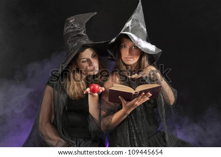 two halloween witches on dark smoky background - stock photo