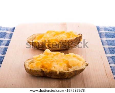 Two halves of a baked potato topped with melted cheese on a wood cutting board - stock photo