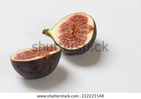 two halves of a cut fig on white background