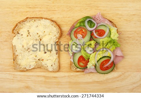 Two halves of a ham salad sandwich on a wooden board - stock photo