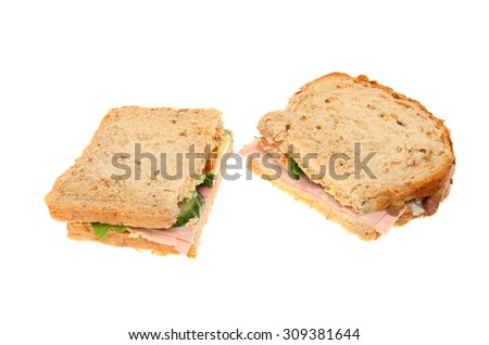 Two halves of a ham sandwich made with multi grain bread isolated against white - stock photo