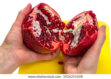 Two halves of a pomegranate in hands on white background