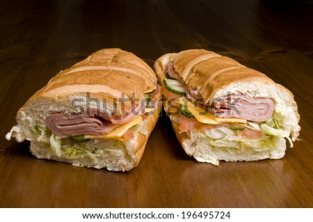 Two halves of a submarine sandwich filled with meat, cheese, cucumber, and lettuce. - stock photo