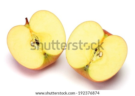 Two halves of an apple that has been cut. - stock photo