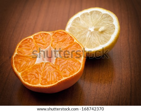 Two halves of ripe orange and lemon on a wooden background. - stock photo