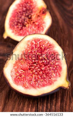 Two halves of sliced fresh figs on wooden background close-up