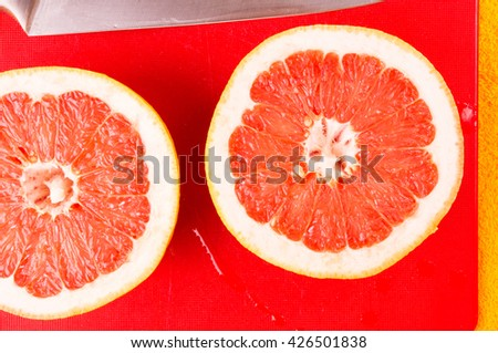 two halves of the grapefruit and the knife on yellow background