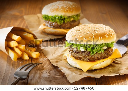 Two hamburger and fries on brown paper and wooden table - stock photo