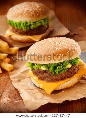Two hamburgers and french fries on brown paper