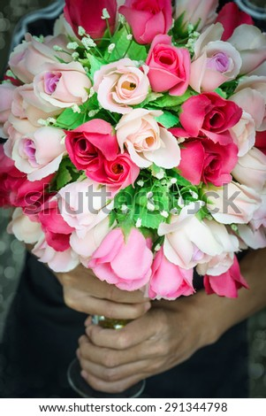 Two hand holding colorful bunch rose made from fabric - stock photo