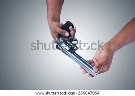 two hand holding gun revolvers on gray background - stock photo