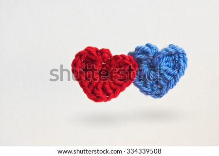 Two hand made crochet knit Red Heart and Blue Heart on white background. Valentines Day, Wedding composition with hearts. - stock photo