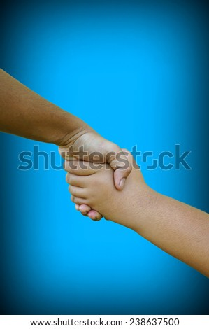Two hand man help each other on blue background - stock photo
