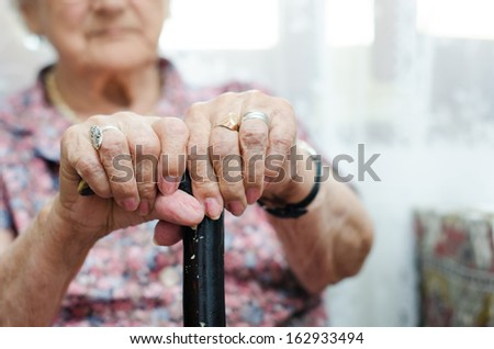Two hand of senior woman sitting in chair holding walking stick - stock photo