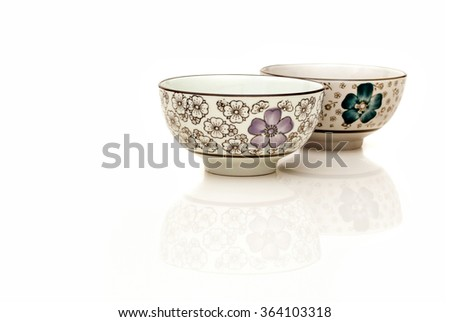 Two hand painted oriental soup bowl on white background with reflection. A bowl is a round, open-top container used in many cultures to serve hot and cold food. - stock photo