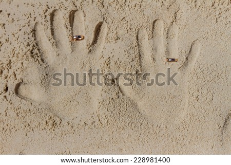 two hand prints with wedding rings on tropical sand beach, outdoor beach wedding concept - stock photo