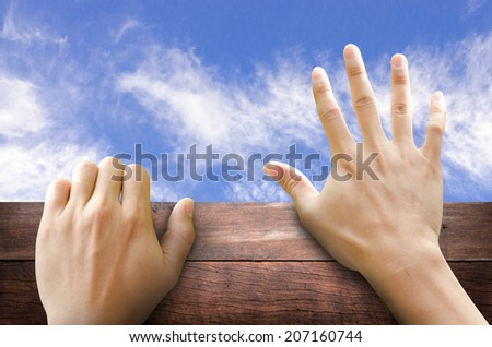 Two hand trying to climb the wooden wall to go out. FREEDOM concept. - stock photo