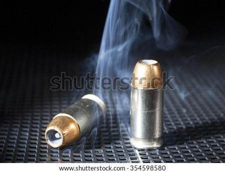 Two handgun cartridges on black with smoke around - stock photo