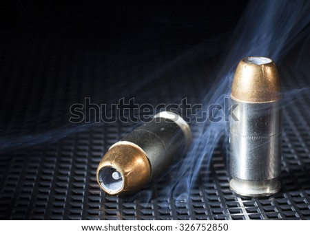 Two handgun cartridges on black with smoke in the background - stock photo